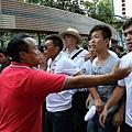 醜聞纏身民望不斷跌落的梁振英8月11日到天水圍出席地區論壇,多個政黨和團體到場示威抗議,場內場外都有黑幫成員  護駕,圖為香港元朗美都餐廳及龍獅隊負責人陳嘉輝(紅衫者)和香港屏山鄉鄉委會主席曾樹和(草帽者)現場指揮黑道  人士圍毆抗議人士。(潘在殊/大紀元)