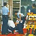 ■遭兩警開槍轟斃的何世通倒地,救護員檢查其傷勢。