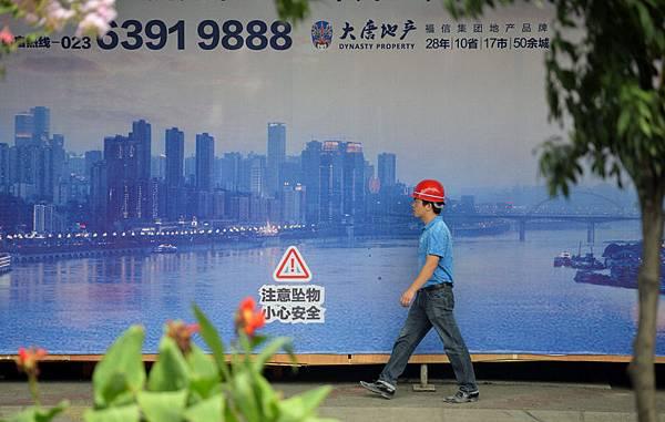 重慶市位於中國的西南方,根據官方資料,它的人口有2,900萬人,而非官方的人口資料則是3,200萬人,它是世界上成長最快速、人口最多中的一個城市。圖為2013年8月8日,重慶,一位建築工人經過一個建造重慶的大廣告牌。(Getty Images)