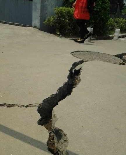 5月14日,南京江寧區一小區的高層住宅樓因地面下沉,造成牆體與路面間地面開裂,裂口清晰可見。(網絡圖片)