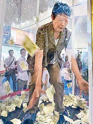 2014廈門春季房地產展示交易會開幕時,有商家設置「搶錢機」,市民在機內搶得的人民幣可歸其所有。(網絡圖片)