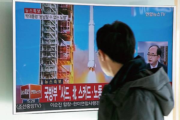 韓國首爾民眾從電視上看到北韓2月7日又以發射衛星之名,進行遠程導彈發射試驗的新聞報導。(Getty Images)