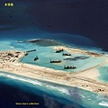圖為中國大陸派遣大批船隻,運送大量物資,在永暑礁興建港口和一條3千公尺的飛機跑道。(網路圖片)