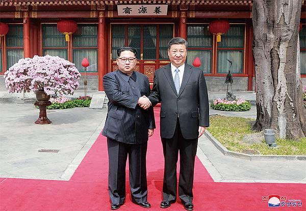 近日,金正恩密訪北京,而他與被北韓稱之為「千年宿敵」的中國領導人習近平尷尬握手的照片也在各大媒體廣傳。(AFP)