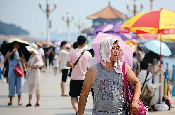 2018年8月1日,青島棧橋的遊客用毛巾遮陽防暑。(大紀元資料室)