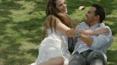 stock-footage-happy-beautiful-young-man-and-woman-in-love-lying-on-grass-in-park-slow-motion