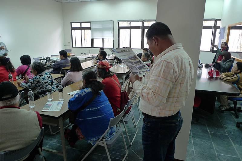 顏技士觀看六龜重建關懷協會發刊的社區報