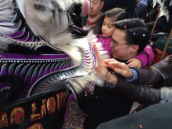 大人小孩都伸長了手想要摸一摸獅子頭得個好彩頭