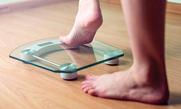Female_feet_standing_on_electronic_scales.jpg