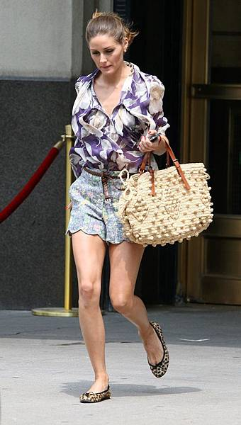 Fashionista Olivia Palermo, wearing a purple floral blouse with tiny shorts featuring a clamshell hem, leopard flats, and a woven bag walks home