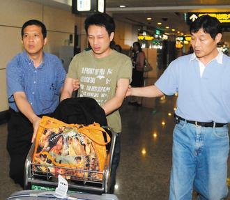 領隊洪佳榮(中)昨天下午搭機回台時,涉嫌在行李轉盤竊取邱姓男子的行李箱,被埋伏守候的航警局刑警隊幹員逮捕。