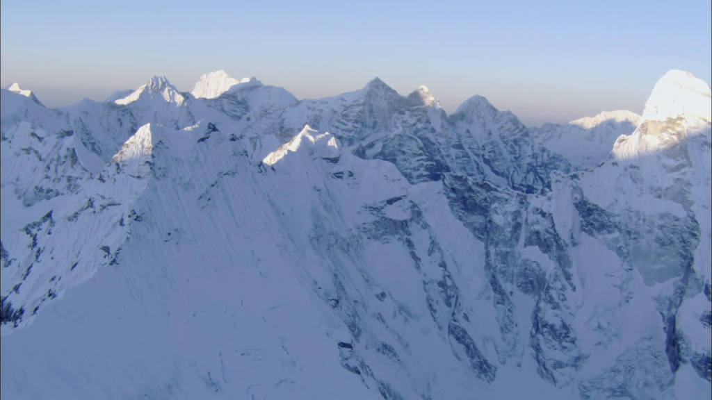 snow-himalaya-mountain-peak-a-high-elevated-view-of-powder-snow-white-blanketed-mountain-peaks-sheer-rock-cliffs-and-jagged-ridge-lines-extend-into-blue-skies_r1wbry1mw__F0000.png