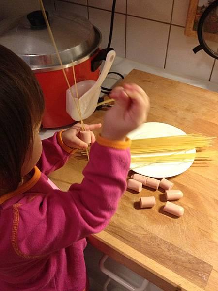 Ida 自己學著將義大利麵條串入香腸中