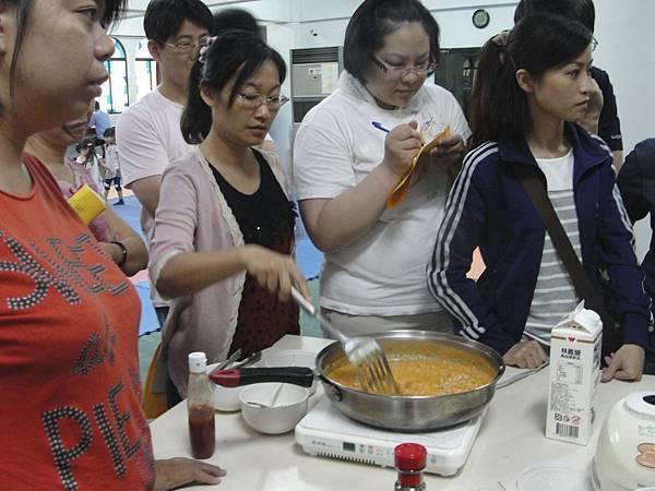 熱心的家長幫忙照顧香味四溢的義大利肉醬醬料