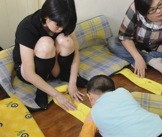 兒子畫,媽媽幫忙壓著紙捲