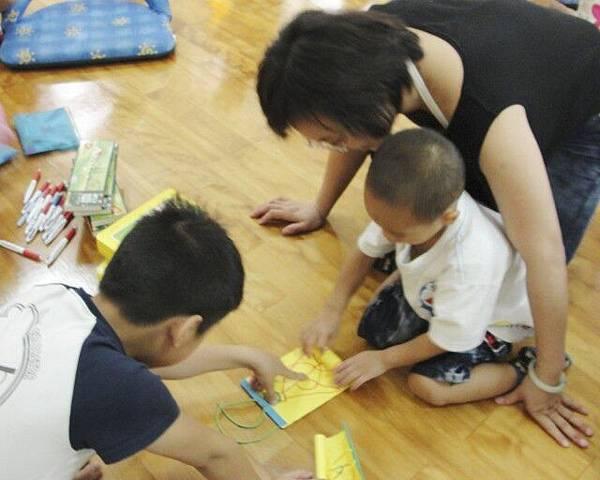 害羞的弟弟由媽媽陪著拿迷宮給別人玩