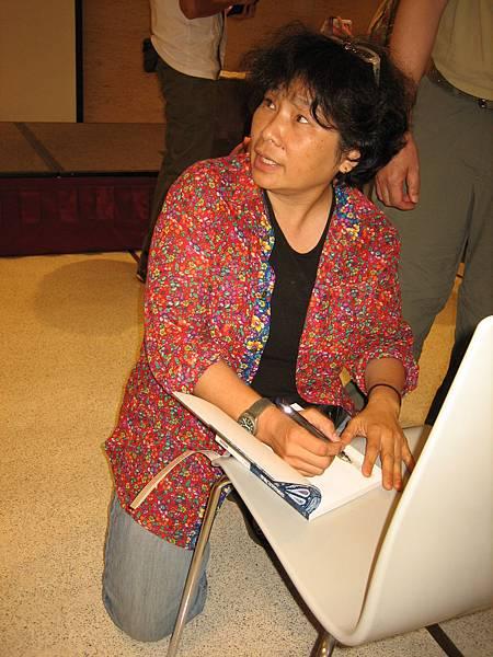 有人找張桂越簽書,她身旁沒桌子,索性跪在椅子前簽