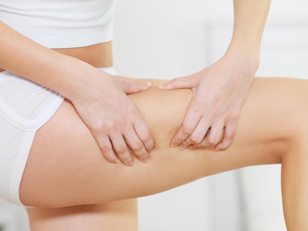 female-squeezes-cellulite-skin-her-legs.jpg