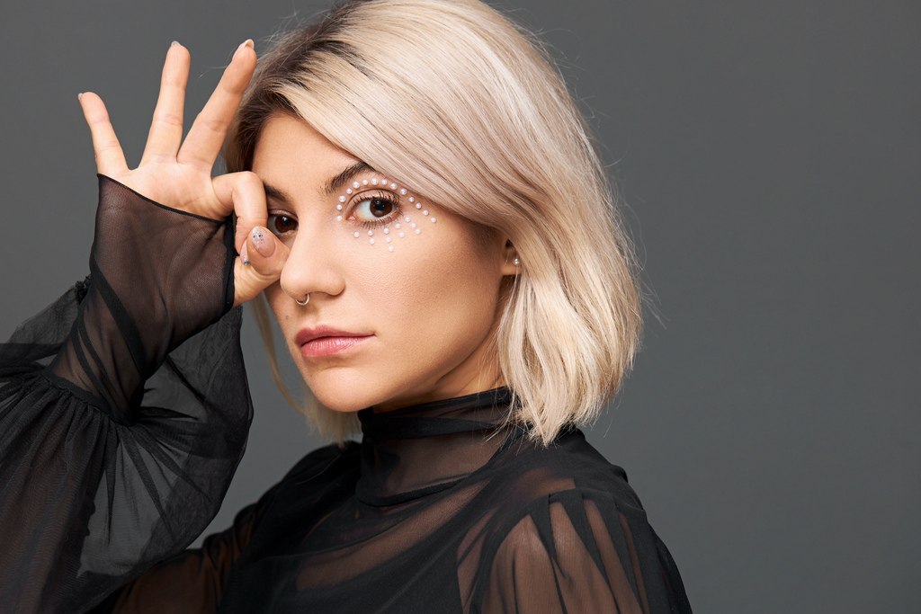 mysterious-beautiful-young-caucasian-female-with-artistic-bright-make-up-nose-ring-wearing-trendy-transparent-blouse-with-enigmatic-look-making-gesture-with-fingers-her-eye.jpg
