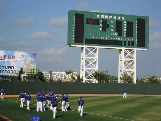 外野記分板與熱身中的航空城棒球隊.JPG