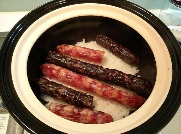 將肝腸,臘腸舖在大火煮6分鐘的米飯上