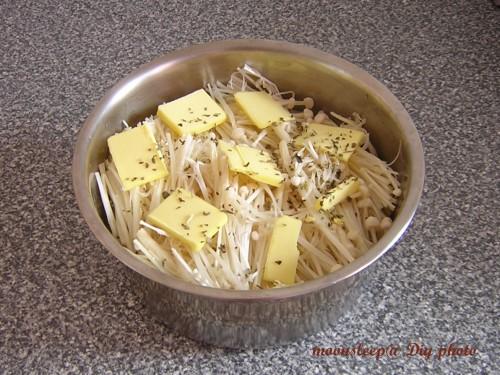 在生米上鋪滿金針菇及奶油薄片,按下開關煮20分鐘