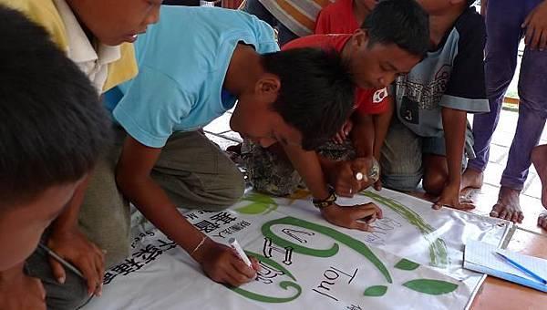 孩子們在活動布條上簽名2.JPG