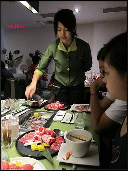 服務生正努力示範如何烤出好吃的肉~