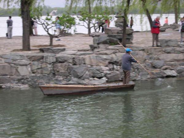 他不是在划船..是在湖面撿拉圾