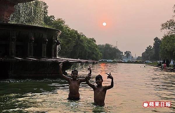 夕陽西下,印度門旁水池裡小朋友開心的戲水,見到鏡頭立即大方擺姿勢。 2016 蘋果日報/楊沛騏。世群旅行社