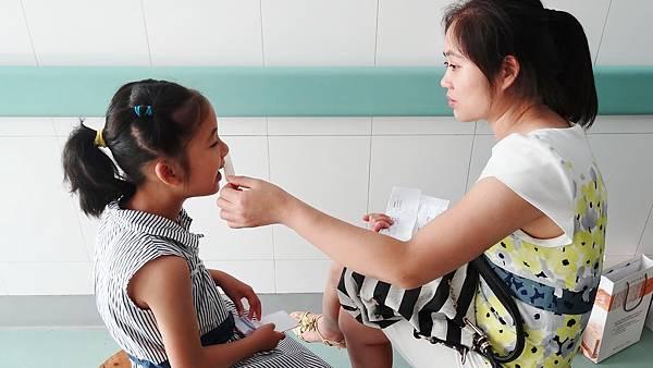 媽媽陪患者做簡單語言治療 (使用鴨舌板矯正基本發音)