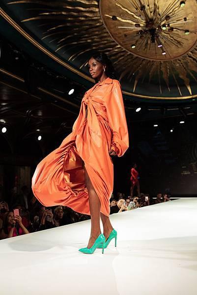 woman-in-orange-long-sleeve-dress-standing-on-white-floor-3011499.jpg