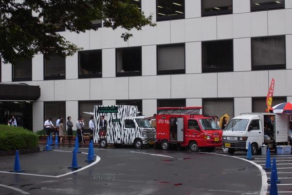 經過路邊辦公大樓前停著餐車,上班族都在排隊