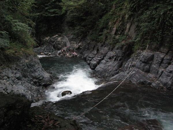 要享受瀑布溫泉,得先拉著繩子渡過這池寒潭