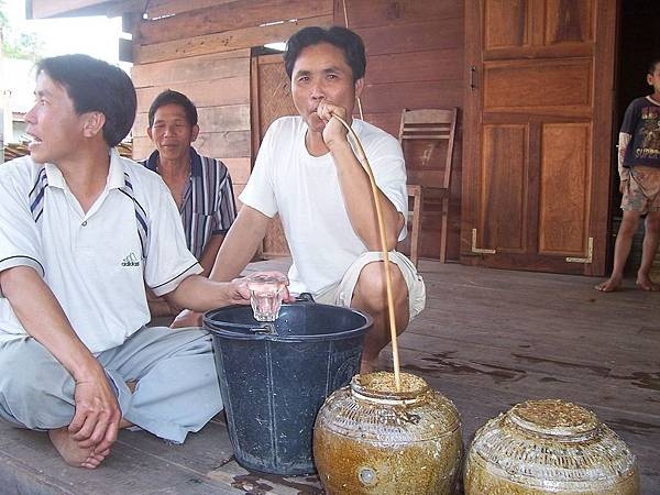 Lao men drinking lauhai or bujkdong (in Khmuic), a type of Lao rice whiskey.jpg