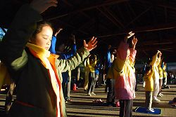 圖:法輪功學員和小弟子在日出的阿里山峰頂的祝山,迎著第一道晨曦煉功弘法。1.jpg