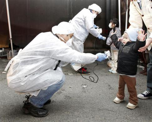 Officials in protective gear check for signs of radiation on children who are from the evacuation area near the Fukushima Daini nuclear plant in Koriyama, March 13, 2011. REUTERS/Kim Kyung-Hoon