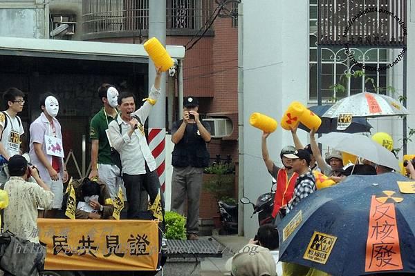 遊行隊伍在金門台灣電力公司前上演行動劇拋出象徵核廢料的圓筒