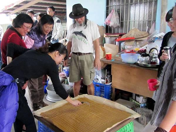 照片2,體驗者為熬煮完成的黑糖畫上橫直線,以利糖塊的剝折。