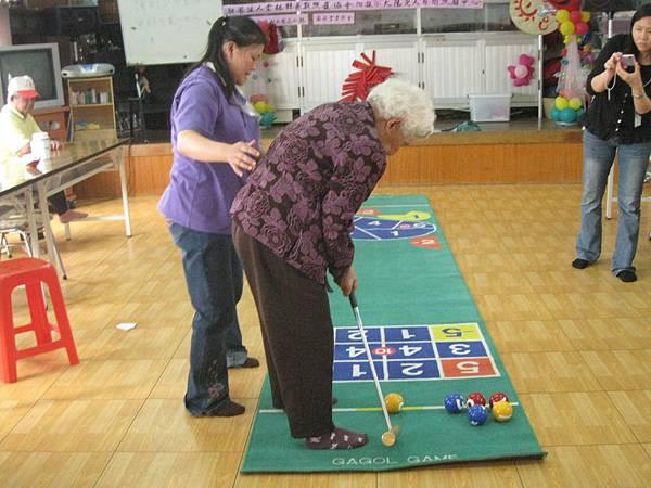 服務人員帶長輩做適宜老人的槌球運動