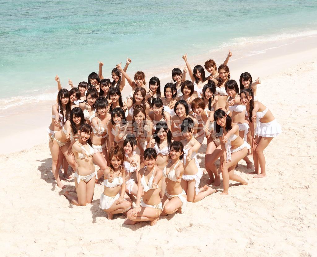 新曲「真夏のSounds good!」に参加した白いビキニ姿のAKB48選抜メンバー36人。グアムの青い空と海を背に、砂浜でキュートに歌い踊った