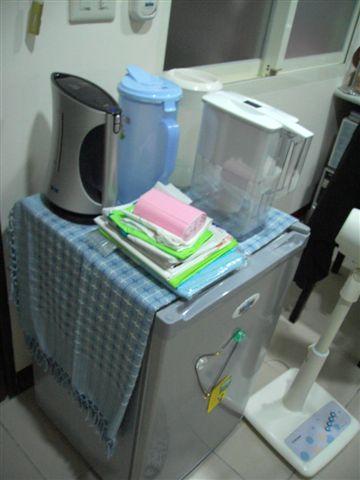 小冰箱,上面有水壺、電熱壺、濾水壺。
