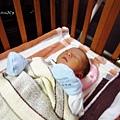 躺在嬰兒床裡,枕頭像是法輪在後頭轉