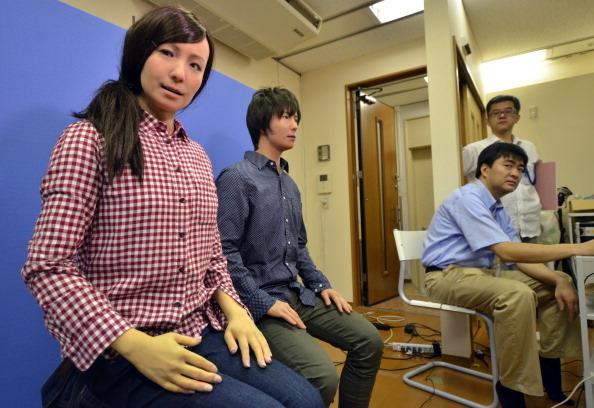 2014年7月8日,日本國家先進工業科技研究所研究員Yoshio Matsumoto(右)在試驗展示他打造的雙胞胎機器人「Actroid F」。