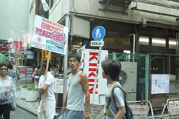 路上的行人,看板上寫 的應該是 曬成小麥肌色的沙龍店