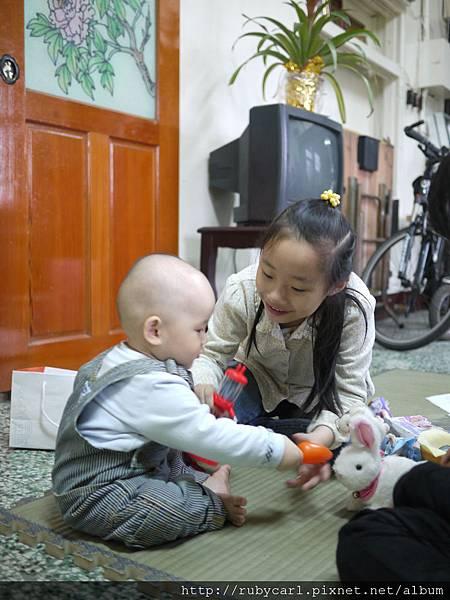 姊姊在教巧虎餵兔子吃紅蘿蔔