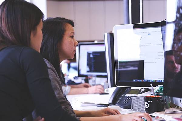 female-colleagues-working-on-computer-sitting-at-office-desk.jpg