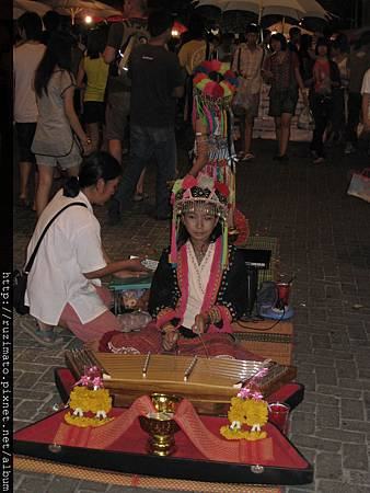 Girl performs in Chiang Mai Sunday Market with tribal folk apparel