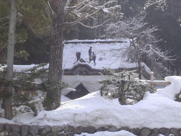 神社正在鏟屋頂的雪