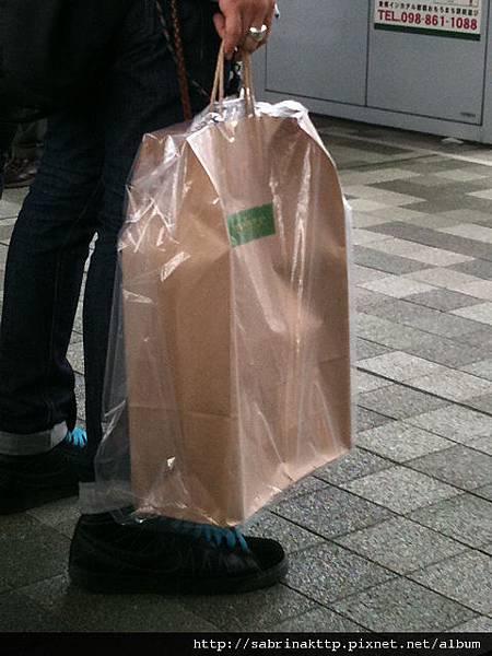 IMG_3163在Okinawa的首里站等車的時候,外頭下著雨,一位乘客的提袋,吸引了我的視線。這是商家貼心的、服務周到的為顧客的提袋也穿上雨衣嗎?